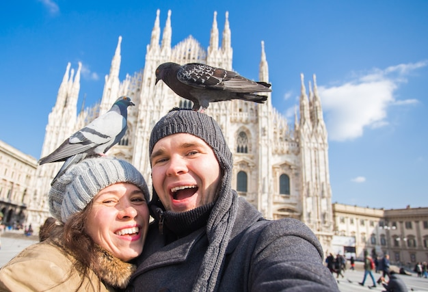 Концепция зимних путешествий и каникул - счастливые туристы, делающие автопортрет с забавными голубями в
