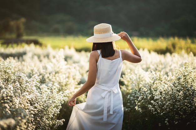 冬の旅行リラックス休暇の概念、タイ、チェンマイの庭の花畑のドレス観光で若い幸せな旅行者アジアの女性