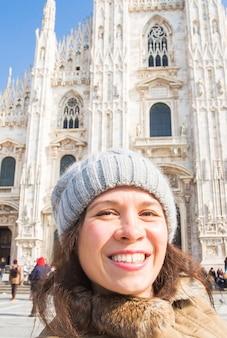 겨울 여행, 휴가, 휴일 개념 - 이탈리아 밀라노 대성당 두오모 디 앞에서 셀카를 찍고 있는 웃고 있는 젊은 여성.