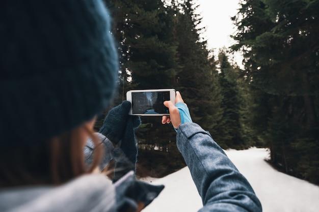 Концепция зимнего путешествия - женщина вид сзади, снимающая зимний лес на смартфон