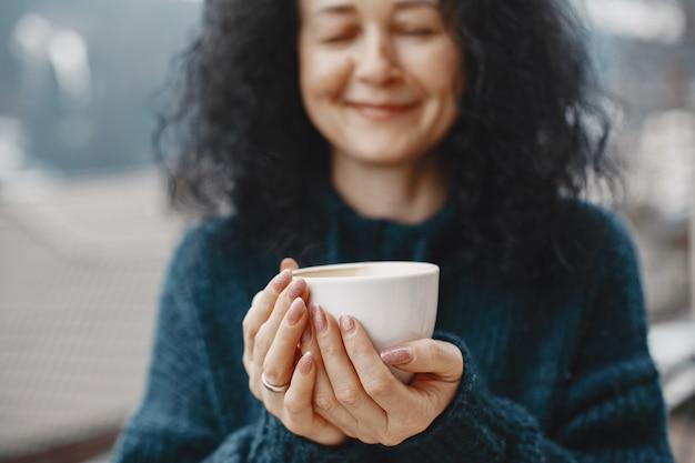 산에서 겨울 방학. 여성의 곱슬 머리. 커피와 함께 흰색 컵입니다.
