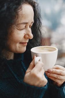 山での冬休み。女性の巻き毛。コーヒーと白いカップ。