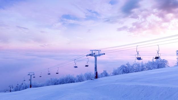 Зимний отдых в горах горнолыжного курорта. опора подъемника на рассвете покрыта снегом и инеем.