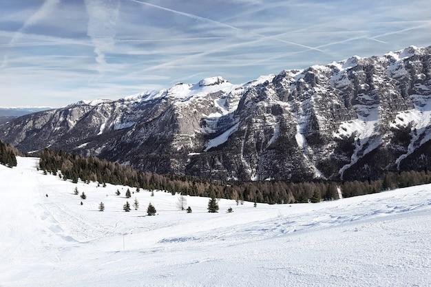 冬。スキー場の麓にある、ドロミテの雪に覆われた崖と森のある道の景色。