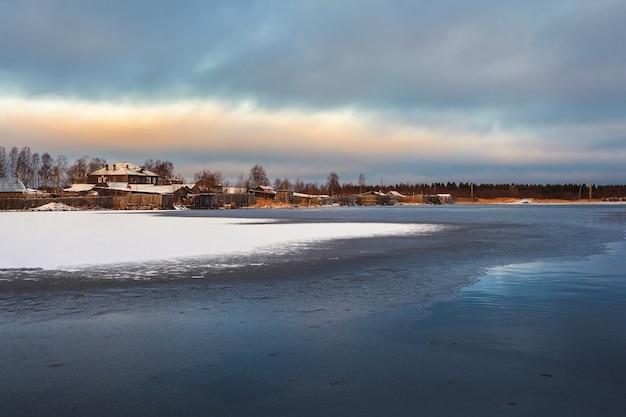 Зимний вид со старых домов возле заснеженного озера. аутентичный северный город кемь зимой. россия.
