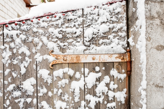 Winter in the village. wooden frozen fence. snow and icicles are everywhere.
