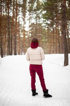 눈 덮인 숲에서 겨울 산책, 빨간 점프 슈트와 재킷을 입은 소녀가 자연의 키 큰 나무 사이를 산책합니다.