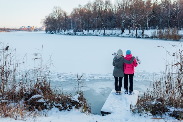 Winter walk. mother and adult daughter admire snowy lake landscape. family hugging, relaxing during holidays