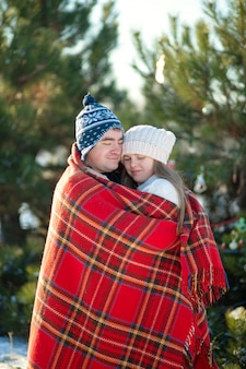 Winter walk through the woods, the guy in the red plaid blanket wraps the girl up so she gets warm