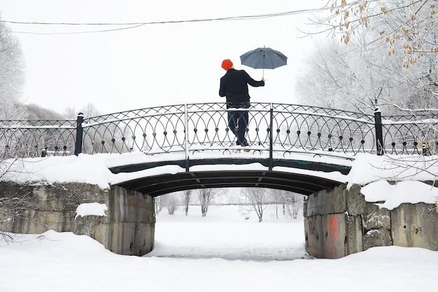 우산으로 겨울 산책. 우산을 쓴 코트를 입은 남자, 겨울 풍경, 겨울 전망을 배경으로 산책