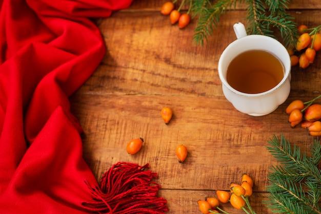 겨울, 따뜻한 분위기. 나무 배경에 빨간 스카프, 장미 열매, 가문비나무가 있는 뜨거운 홍차 한 잔 겨울 아늑한 저녁입니다. 플랫 레이, 레이아웃, 텍스트 배치, 엽서, 고해상도