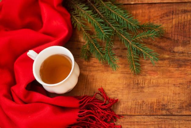 겨울, 따뜻한 분위기. 나무 배경에 빨간 스카프와 가문비나무가 있는 뜨거운 홍차 한 잔