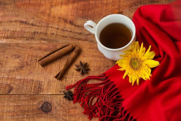 겨울, 따뜻한 분위기. 나무 배경에 빨간 스카프, 계피 스틱, 해바라기를 넣은 뜨거운 홍차 한 잔