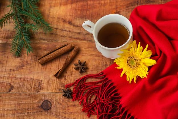 겨울, 따뜻한 분위기. 나무 배경에 빨간 스카프, 계피 스틱, 가문비나무, 해바라기를 넣은 뜨거운 홍차 한 잔