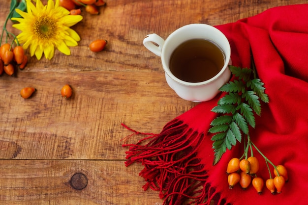 겨울, 따뜻한 분위기. 나무 배경에 빨간 스카프, 녹색 잎, 장미 열매, 해바라기를 넣은 차 한 잔. 겨울 저녁입니다. 플랫 레이, 레이아웃, 텍스트 배치, 엽서, 고해상도