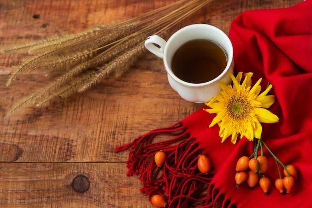 겨울, 따뜻한 분위기. 나무 배경에 빨간 스카프, 장미 열매, 밀 이삭, 해바라기를 넣은 차 한 잔. 겨울 저녁입니다. 플랫 레이, 레이아웃, 텍스트 배치, 엽서, 고해상도