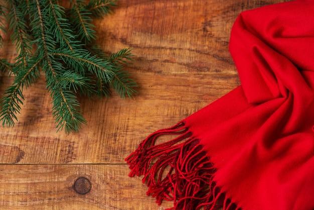 겨울, 따뜻한 분위기. 나무 배경에 빨간 스카프와 가문비나무가 있는 프레임. 겨울 저녁입니다. 플랫 레이, 레이아웃, 텍스트 배치, 엽서, 고해상도