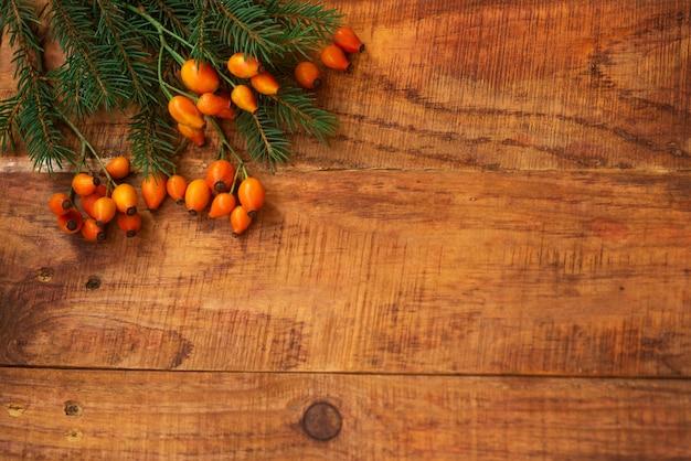 겨울, 따뜻한 분위기. 나무 배경에 빨간 스카프, 장미 열매, 가문비나무가 있는 프레임. 겨울 저녁입니다. 플랫 레이, 레이아웃, 텍스트 배치, 엽서, 고해상도