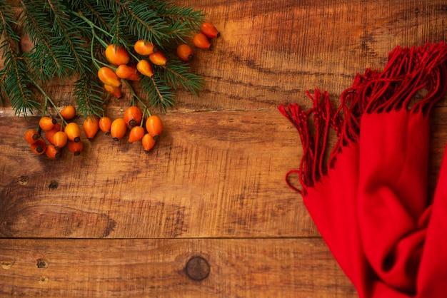 겨울, 따뜻한 분위기. 나무 배경에 빨간 스카프, 장미 열매, 가문비나무가 있는 프레임