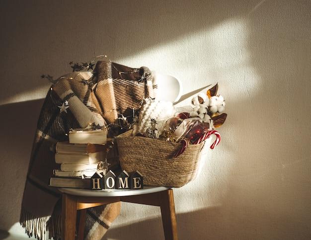クリスマスの装飾のバスケットと椅子の上の冬の暖かい毛布