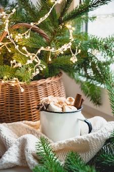 Winter warming mug of chocolate with marshmallow on windowsill