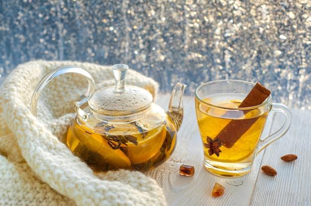 Зимний согревающий чай с лимоном и апельсином на фоне морозных узоров.