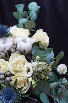 Winter wedding bouquet of white roses, cotton and eringium on a black . the bride's bouquet.