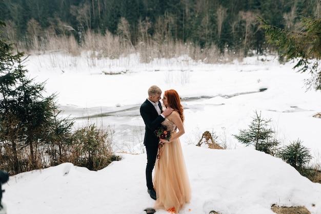Зимняя свадьба, стильная молодая пара в лесу, нежные объятия на берегу реки