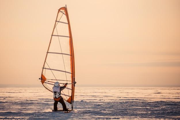 겨울 윈드 서핑. 일몰에 눈 속에서 서핑을 타는 남자. 극한의 겨울 스포츠. 후면보기