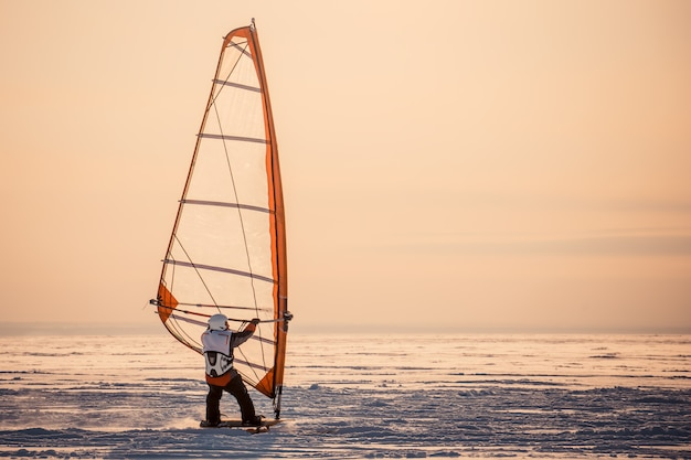 Winter windsurfing. man riding a surf in the snow at sunset. extreme winter sport. the rear view