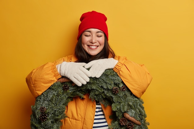 Winter woman has toothy smile, buys green wreath, wears red hat, yellow coat and white gloves, anticipates for christmas eve, poses against yellow wall.