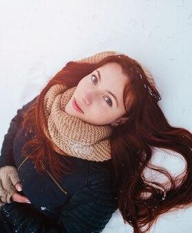 겨울. 카메라를보고 귀 머프를 입고 붉은 머리를 가진 여자.