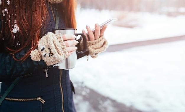 Зима. женщина с рыжими волосами в перчатках. девушка пьет горячий чай или кофе с чашкой изолированной утюгом. он использует телефон или смартфон. играю, люби что-нибудь в интернете. прокручивает новостную ленту