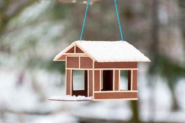 Зимняя деревянная кормушка для птиц крупным планом, покрытая снегом