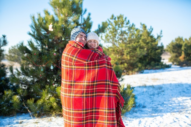 Winter in the woods a guy wraps his girlfriend in a warm red checkered plaid so that she warms herself