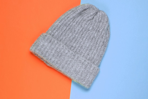 Winter woolen hat on a colored paper background