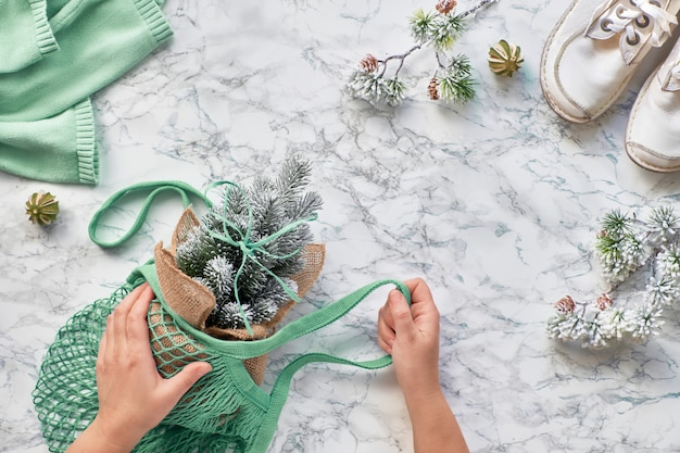 Wintertime, creative flat lay with artificial plastic christmas tree in eco friendly greeen mint color string bag