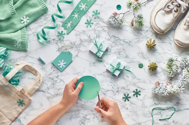 Wintertime, creative flat lay with various winter decorations, christmas tree twigs and hands cutting tags