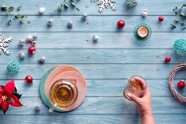 Зимний чай, плоская композиция со стеклянным чайником, стакан чая в руке на выцветших синих деревянных досках.