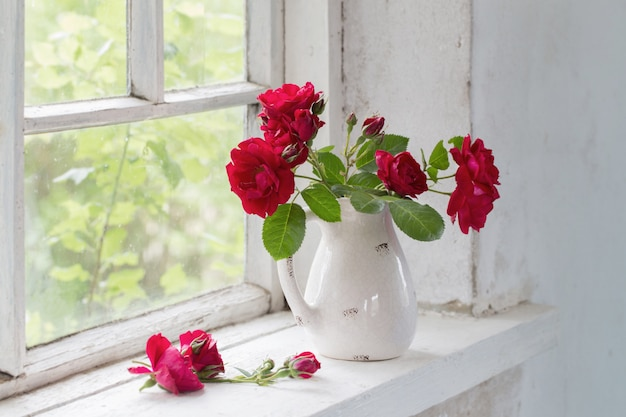 Красные розы в кувшине на winwowsill