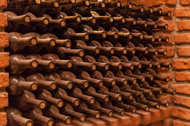 Винные бутылки лежат на кирпичах в подвале, старые винные погреба с бутылками и бочками