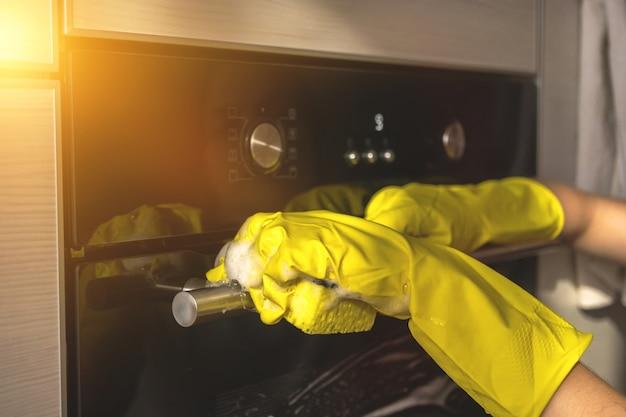 노란색 고무 장갑과 스폰지로 가정 부엌에서 오븐 문 닦고 청소하기