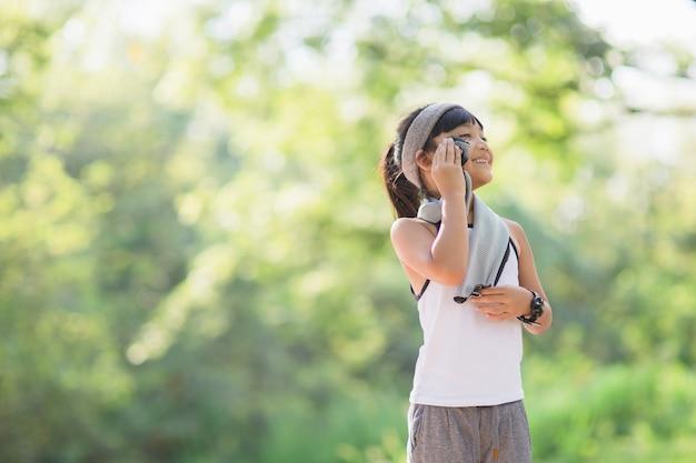Вытирание пота детей бегуном после тренировки. дети, тренирующиеся в городском парке на открытом воздухе.