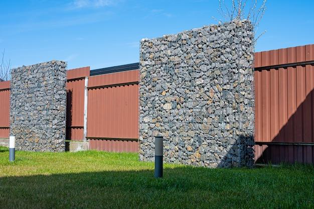 철사와 돌 담. 돌 gabion으로 만든 장식 건물입니다.