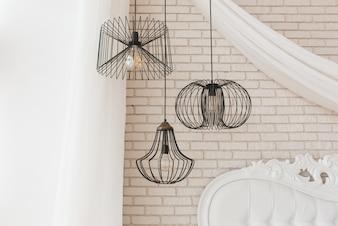 Wire black design ceiling luster hanging in bedroom. Loft interior details