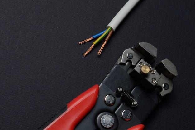 ワイヤーカッターと剥ぎ取られたワイヤーは暗い背景に横たわっています。閉じる。