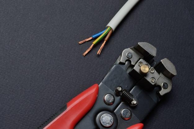 ワイヤーカッターとそれらで剥ぎ取られたワイヤーは黒い背景の上にあります。閉じる。