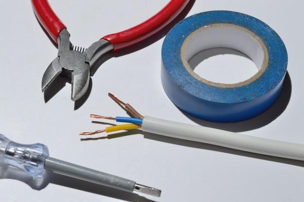 白い背景の上のワイヤーカッター、ワイヤー、電気テープ。上面図。