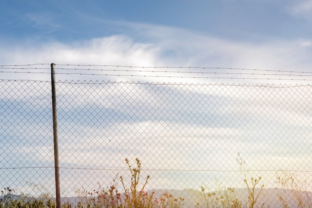 Wire fence with a blue sky with clouds
