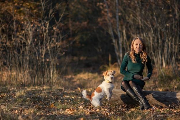 철사 머리 잭 러셀 테리어 강아지는 가을 공원에서 소녀의 발 앞에 서 있습니다